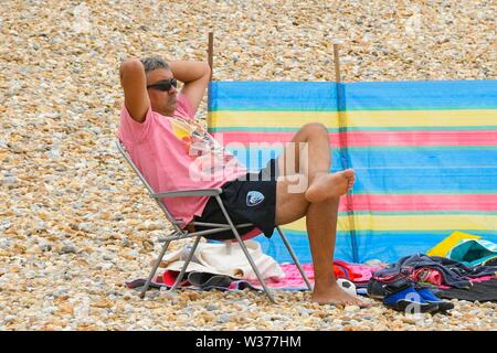 Lyme Regis, Dorset, UK.  13th July 2019. UK Weather.  A man relaxes on the beach at the seaside resort of Lyme Regis in Dorset on a warm cloudy day.  Picture Credit: Graham Hunt/Alamy Live News - Stock Image