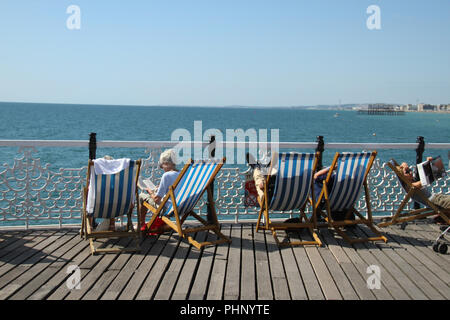 Brighton, UK - September 1 2018: People bask in the sun on the Brighton Palace Pier on a sunny afternoon on 1​ September 2018.   The Pier, in the central waterfront section, opened in 1899 houses amusement rides as well as food kiosks .Credit: David Mbiyu/Alamy Live News - Stock Image