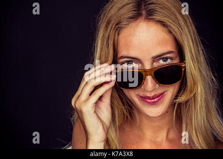 Young woman peeking over top of sunglasses, portrait - Stock Image