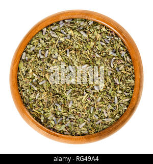 Herbes de Provence in wooden bowl. Mixture of dried herbs of the Provence, France. Savory, rosemary, thyme, lavender, oregano and marjoram. - Stock Image