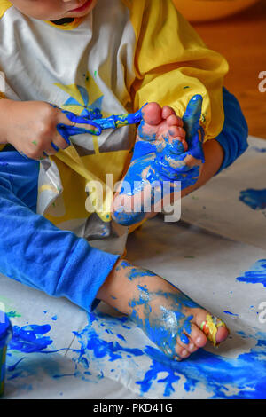 child painting it´s feet - Stock Image
