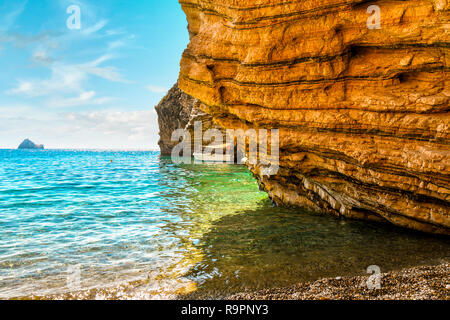 A small boat docks against a rocky cove at Chomi Beach, also known as Paradise Beach, on a sunny summer day on the Greek island of Corfu, Greece. - Stock Image
