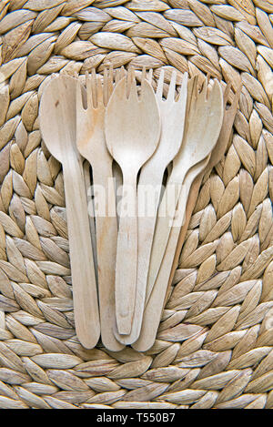 Wooden Cutlery, forks and spoons on leaf placemat - Stock Image