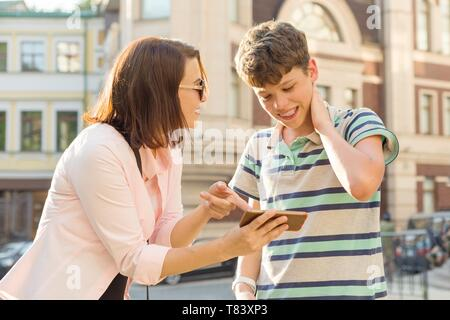 Parent and teenager, relationship. Mother shows her son something in mobile phone, boy is embarrassed, smiling, holding his hands on his head, city st - Stock Image