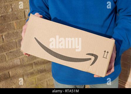 Man holding Amazon box England UK United Kingdom GB Great Britain - Stock Image