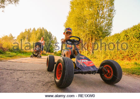 Sarbinowo, Poland - August 9, 2018: Young boy steering a pedal go kart on a small road. Woman with baby buggy walking behind the child. - Stock Image