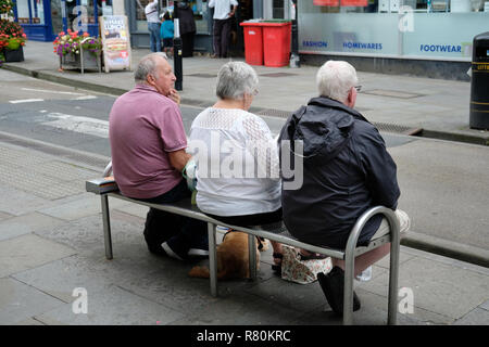 Three pensioners sitting on a bench on a hight street in Wells, Somerset. - Stock Image