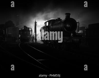 Ex GWR locomotives at night on shed at Didcot Railway centre in a re-created scene reminiscent of the days of steam. - Stock Image