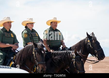U.S Border Patrol agents on horseback listen as President Donald Trump remarks during a visit to the Border Patrol Calexico Station April 5, 2019 in Calexico, California. Trump visited the section of wall at Calexico that was part of a replacement project started under President Obama. - Stock Image