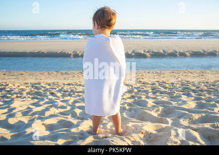 Happy little boy wrapped in a towel after swiming. Sunset shot - Stock Image