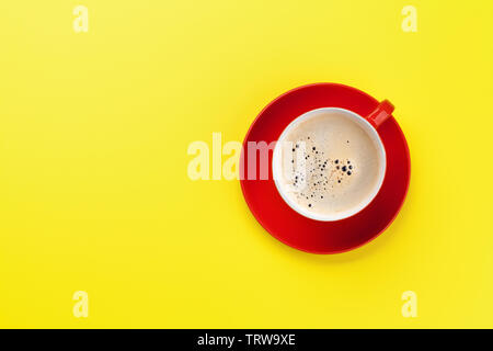 Red coffee cup over yellow background. Top view flat lay with copy space - Stock Image