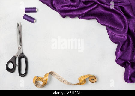 violet cloth, scissors, thread on a light background. view from above.  copy space - Stock Image