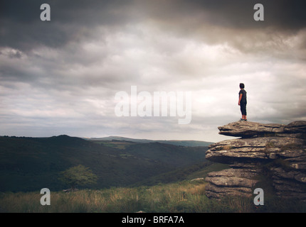 boy stood on the rocks looking over moors - Stock Image