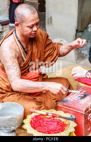 Angkor Wat, Cambodia - 11th January 2018: Monk giving blessings and tying good luck string bracelets. This is in exchange for donations. - Stock Image