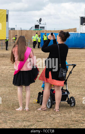 A mother and daughter at an outdoor event with the mother using her mobile phone to take a picture - Stock Image