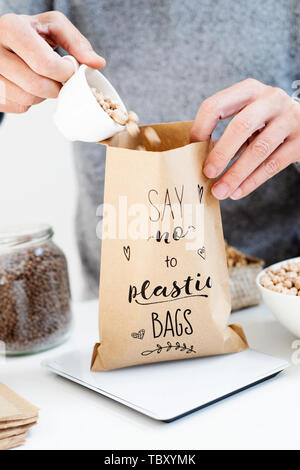 closeup of a caucasian man putting some dry chickpeas on a brown paper bag, with the text say no to plastic bags written in it, placed on an electroni - Stock Image