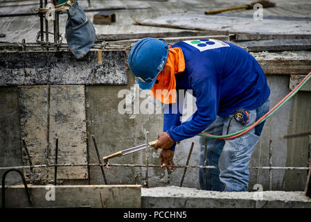 Builder using oxy acetylene torch on a construction site. Thailand Southeast Asia - Stock Image