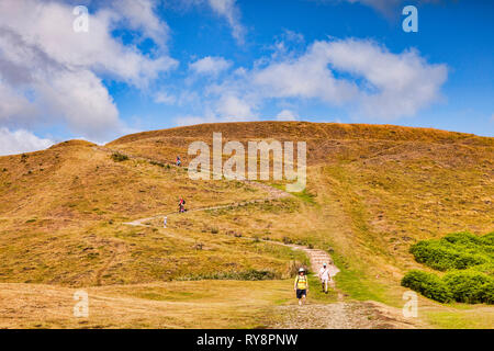 Hikers walking down from Millenium Hill, Malvern Hills, Herefordshire and Worcestershire, England - Stock Image