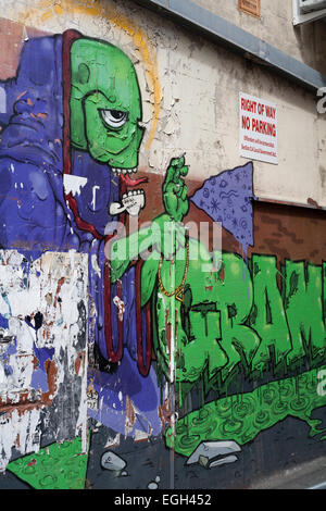 Graffiti image of a humanoid being on an alley wall next to a no parking sign in the city of Perth, Western Australia. - Stock Image