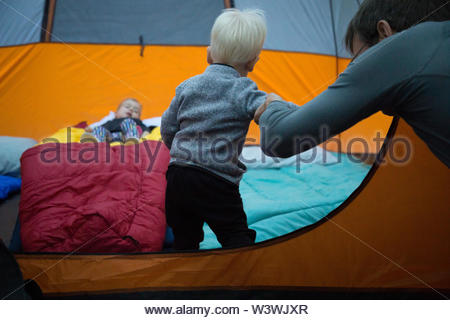 A yound boy explores a tent for the first time with his grandfather and sister. - Stock Image