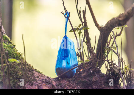 Bag of dog faeces left on a tree in the Peak District - Stock Image