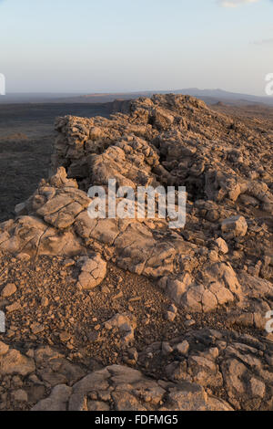 Late sun lights up one side of the cliff edge of the Erta Ale volcano - Stock Image