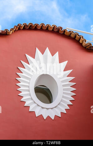 Star pattern around a circular window on the side of a building in Italy - Stock Image