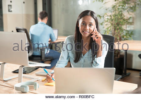 Mid adult woman using smart phone at desk - Stock Image
