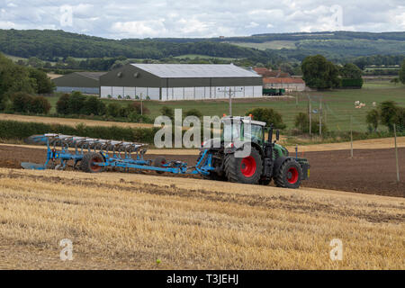A tractor plowing a field in the countryside of North Yorkshire in the United Kingdom. - Stock Image