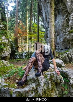Young beauty female teenager girl in nature sitting on big rock very sad and lonely - Stock Image