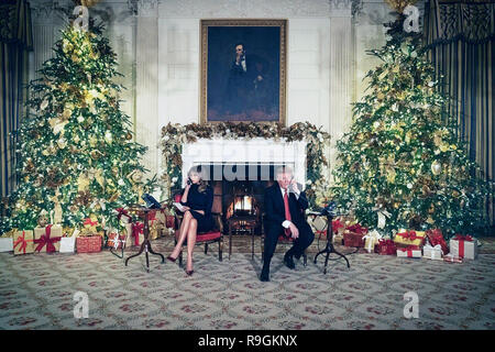 Washington, United States Of America. 24th Dec, 2018. U.S. President Donald Trump and First Lady Melania Trump take calls from children during the annual NORAD Tracks Santa on Christmas Even in the East Room of the White House December 24, 2018 in Washington, DC. The First Lady returned from Palm Beach to join the President who was alone at the White House after shutting down the government in a budget standoff over his border wall. Credit: Planetpix/Alamy Live News - Stock Image