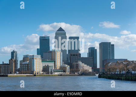 The skyline of the modern financial district Canary Wharf in London with the River Thames in the foreground - Stock Image