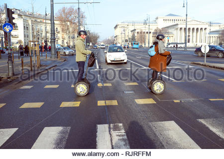 Tourist sightseeing Segway users cross the road towards Heroes' Square in Budapest, Hungary. - Stock Image