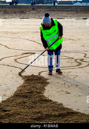 Redcar North Yorkshire, UK. 11th Nov, 2018. The 100th Anniversary of the armistice that ended the First World war.  The Pages of the Sea Project, masterminded by Danny Boyle, had portraits of war casualties carved into the sand on beaches around the UK, to be washed away at high tide.  At Redcar the subject was Theophilus Jones who died on 16/12/1914 during the bombardment of Hartlepool. Local people were also encouraged to make sand images of relations who died in the war.  Many of these were made with help from the organisers, who provided templates. Credit: Peter Jordan_NE/Alamy Live News - Stock Image