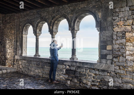 Man male tourist taking pictures with a phone from the loggia of San Pietro, Portovenere, Cinque Terre, Liguria, Italy - Stock Image