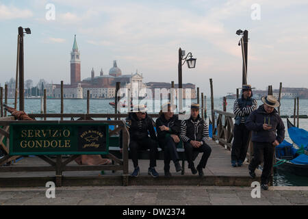 Venice, Italy. 25th Feb, 2014. Gondoliers relax and await customers at the waters edge across from San Giorgio Maggiore. Venice Carnivale Credit:  MeonStock/Alamy Live News - Stock Image
