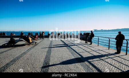 Lisbon, Portugal - Jan 13, 2019: People relax alongside the river Tagus on a sunny winter day - Stock Image
