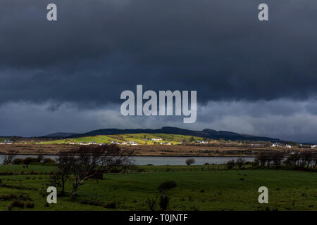 Ardara, County Donegal, Ireland. 20th March 2019. Sunlight creates a dramatic landscape during a passing storm on the north-west coast. Credit: Richard Wayman/Alamy Live News - Stock Image