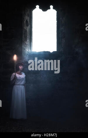 a ghostly woman in a white dress is standing in an old church with a flare - Stock Image