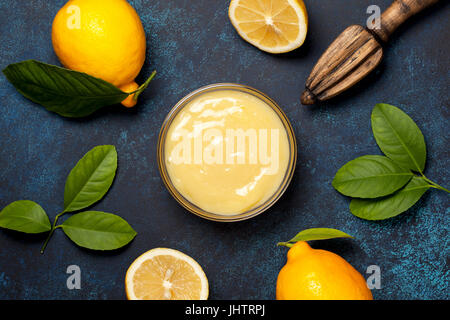lemon curd in a glass bowl, fresh lemons, juicer on a blue background (top view) - Stock Image