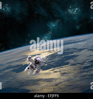 An astronaut floating above Earth. - Stock Image