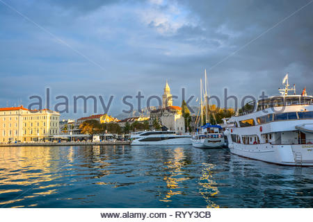 Morning at Riva Harbor on the Adriatic coast of Croatia in the ancient city of Split with boats in the sea and sunlight hitting the Split Cathedral - Stock Image