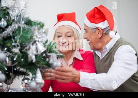 Senior Couple Decorating Christmas Tree - Stock Image