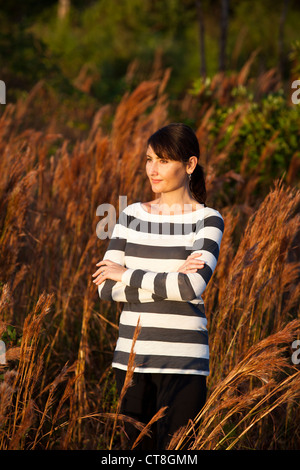 woman folding arms in field - Stock Image