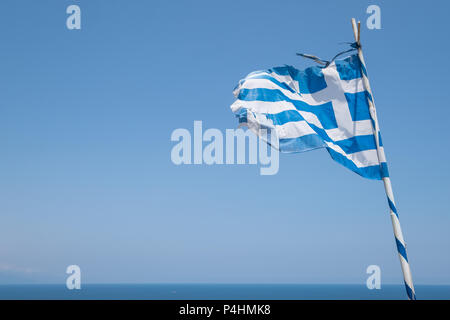 Weathered Greek flag blowing in the wind. - Stock Image