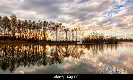clouds reflected on Varese lake at sunset with trees, autumn panorama - Stock Image