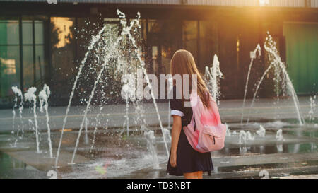 Young schoolgirl with backpack on her shoulders on way home. She stopped to admire fountain. Full-back position. - Stock Image
