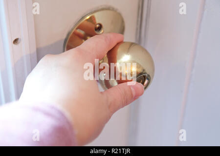 Hand on a gold door knob with thumb pushing the button to lock the door - Stock Image