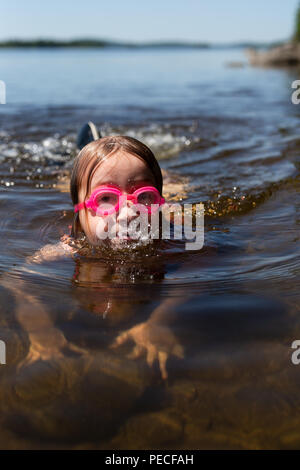 Girl swimming in lake during summer - Stock Image