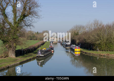 Narrowboats moored on the Grand Union canal at Blisworth Arm on a sunny winter day: Northamptonshire, UK - Stock Image